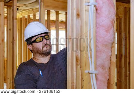 Construction Worker Thermally Insulating Insulation Layer Under House With Glass Wool Soft Focus