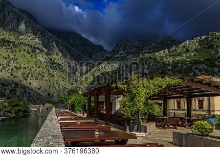 Outdoor Restaurant With A View Onto The Emerald Green Waters Of Kotor Bay And Hillside Of Saint John