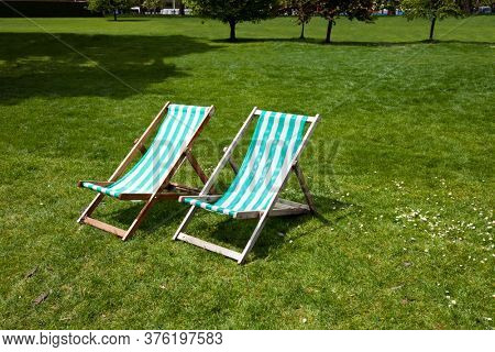 Two deck chairs in a park
