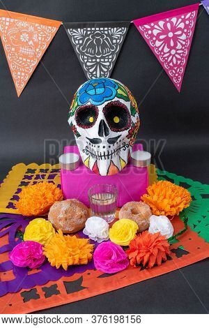 Traditional Mexican Day Of The Dead Offering Altar With Cut Paper, A Hand Painted Skull, Bread, Flow