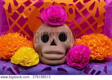 Mexican Day of the dead altar with traditional bread, colorful flowers, a skull, mezcal, candles and