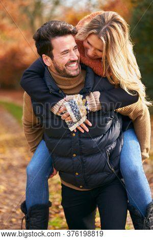 Man Giving Woman Piggyback  As Loving Couple Walking Along Autumn Woodland Path Through Trees