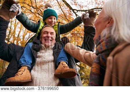Grandparents With Grandson Enjoying Walk Along Autumn Woodland Path Together