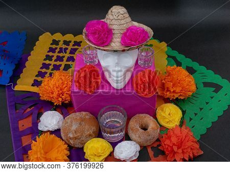 Mexican Day Of The Dead Altar With Traditional Bread, Colorful Flowers, A White Skull With Hat And C