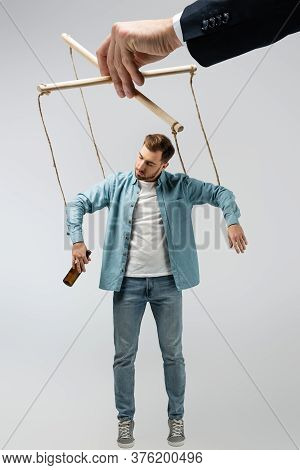 Puppeteer Manipulating Young Man With Bottle Of Beer Isolated On Grey