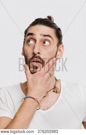 Contemplative young man in white t-shirt with hand on face against white background