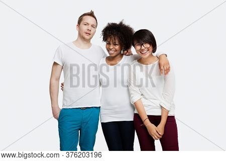 Portrait of happy multi-ethnic friends in casuals with arm around each other over white background