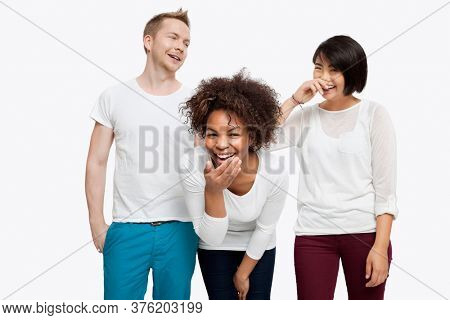 Young multi-ethnic friends in casuals laughing over white background