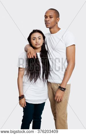 Portrait of serious young couple in casuals standing against white background