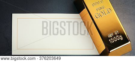 An Ingot Of Gold Metallic Ingot Glittering On A Grey Textured Background And A Card For Lettering.