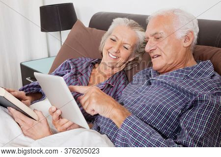 Happy senior couple using digital tablet while lying on bed in room