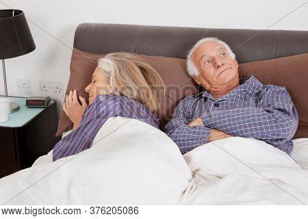 Bored elderly man looking away while spouse sleeping besides in bedroom