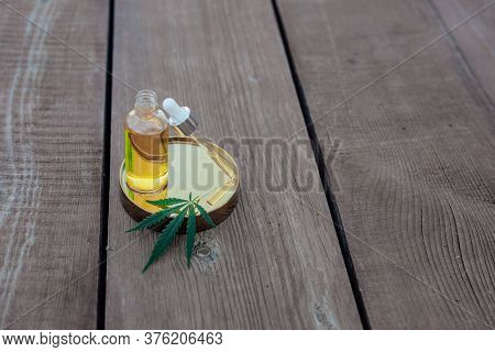 Glass Bottle And Dropper Cbd Oil, Thc Tincture And Cannabis Leaf On Wooden Background. Laboratory Pr