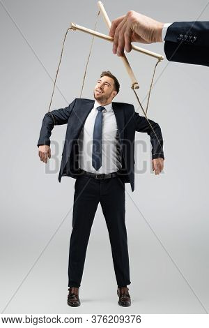 Cropped View Of Puppeteer Holding Smiling Businessman Marionette On Strings Isolated On Grey