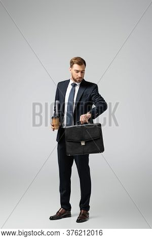 Businessman With Leather Suitcase And Paper Cup Looking At Wristwatch Isolated On Grey