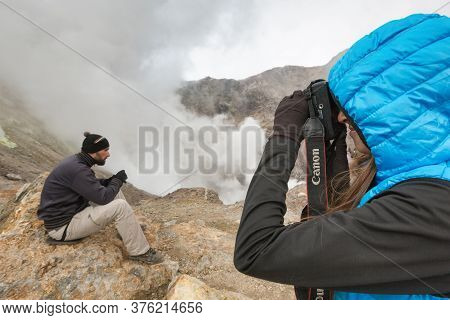 Young Woman Photographs Man In Crater Active Volcano Surrounded By Smoke Hot Springs, Eruption Fumar