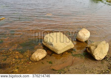 Large Boulders Lie In The Water Against The Backdrop Of Rolling Waves And Muddy Water After A Small