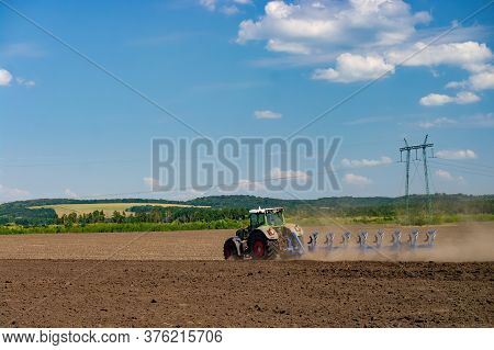 Tractor With A Towed Plow Cultivates The Plowing Of The Field Before The Autumn Sowing. Agricultural