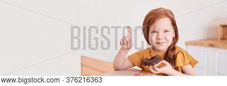 Little Girl Eating Round Doughnut. Pointing Up. Sweet Desert. Unhealthy Food. Home Lockdown Lifestyl
