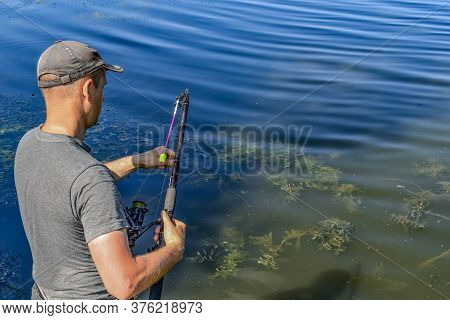 Fisherman Gathers Fishing Rod On A Background Of Blue Muddy Water With Algae - Rear View From Above