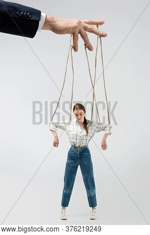 Cropped View Of Puppeteer Holding Marionette On Strings Isolated On Grey
