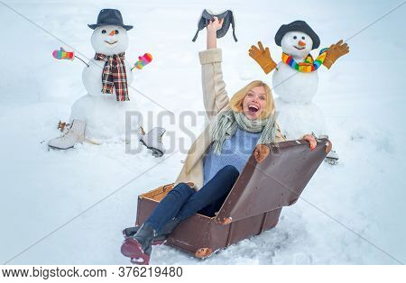 Winter Holiday. Woman With Suitcase On Snowman Background. Winter Holiday Trip Concept. Portrait Of