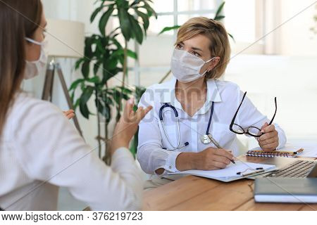 Middle Aged Female Doctor Therapist In Medical Mask On Consultation With Patient In Office.
