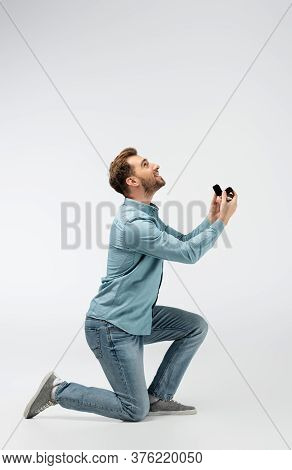 Side View Of Happy Man Doing Marriage Proposal Isolated On Grey