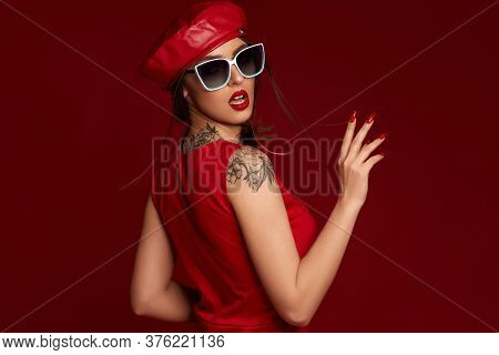 Sexy Brunette Woman In White Sunglasses, Leather Beret And Dress Posing In Studio On Red Background.