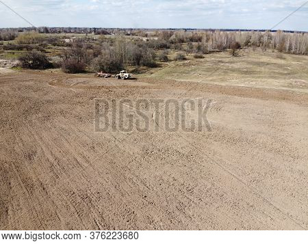 Agricultural Machinery In A Field Near A Small Grove, Aerial View. Agricultural Land.