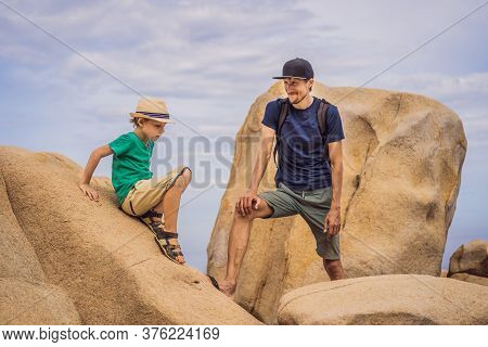 Dad And Son On A Rock. Domestic Vacation Concept