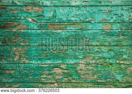 Old Wooden Board With Peeling Paint. Texture Background Of Green Flaky Paint On Cracked Plank Of Woo