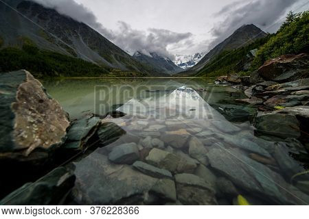 Altai, A Beautiful Mountain Lake Ak-kem With Clear Water And Rocks At The Bottom