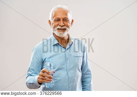 Portrait Of Cheerful Senior Man Who Is Holding Bottle Of Water And Smiling.