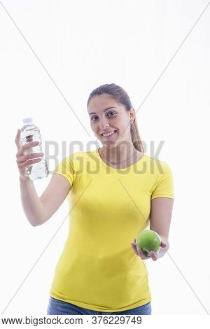 Young Woman Holding A Delicious Green Apple And A Bottle Of Water While Smiling At The Camera.