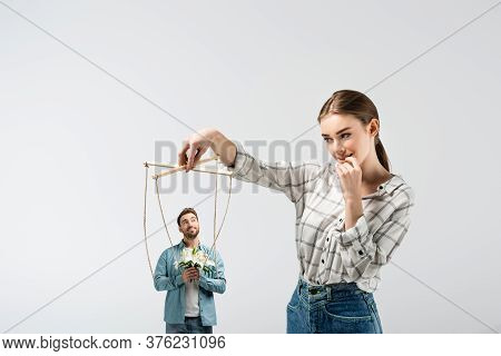 Female Puppeteer Holding Male Marionette With Flowers Isolated On Grey