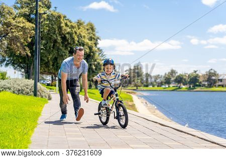 Father Teaching His Son To Ride A Bike And Having Fun Together At The Park