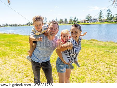 Outdoors Portrait Of Happy Caucasian Family Of Mum Dad, Boy And Little Girl Having Fun In The Park