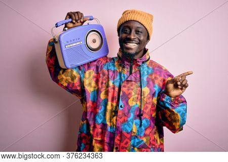 Young african american man listening to music holding portable vintage retro radio very happy pointing with hand and finger to the side