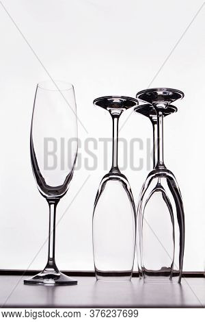 Several Glass Champagne Cups On A White Background. Empty Glassware Placed Upside Down.