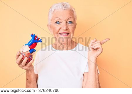 Senior beautiful woman with blue eyes and grey hair holding heart organ smiling happy pointing with hand and finger to the side