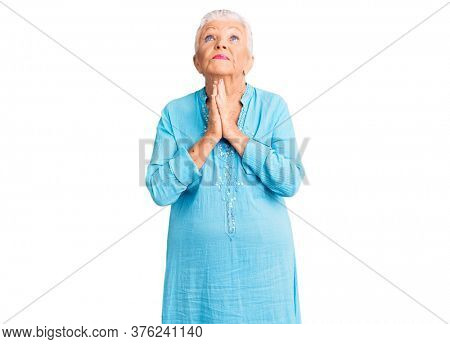 Senior beautiful woman with blue eyes and grey hair wearing summer dress begging and praying with hands together with hope expression on face very emotional and worried. begging.