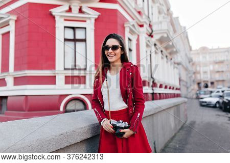 Lovable Slim Girl With Camera Expressing Happiness. Outdoor Photo Of Enthusiastic Female Photographe