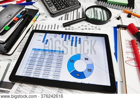 Top view of office employee's desk - work with tablet pc computer and financial reports, analysis and accounting, tables and graphs, various office items for bookkeeping