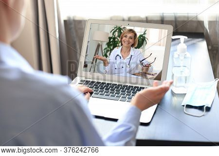 Young Woman Making Video Call With Her Doctor During Self Isolation And Quarantine. Online Consultat