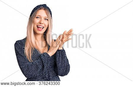 Young beautiful blonde woman wearing casual clothes clapping and applauding happy and joyful, smiling proud hands together