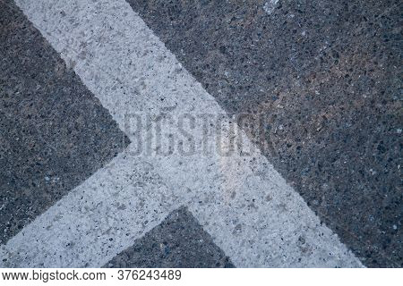 Close Up Of Street Line On Grainy Asphalt. Texture Of Ashpalt With Road Markings.