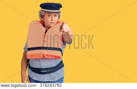 Senior woman with gray hair wearing nautical lifejacket pointing with finger to the camera and to you, confident gesture looking serious