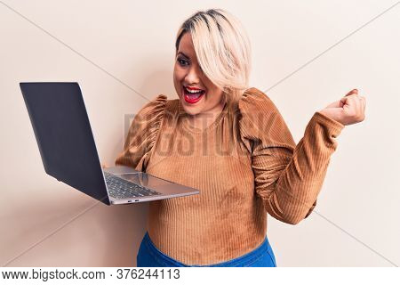 Young beautiful blonde plus size woman working using laptop over isolated white background screaming proud, celebrating victory and success very excited with raised arm