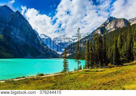 The lake with azure water is surrounded by mountains and forests. Glacial Lake Louise. Sunny day. Travel to the Rocky Mountains of Canada. The concept of ecological, active and photo tourism